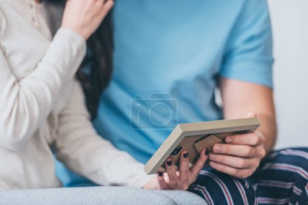 Photo for Cropped view of couple holding picture frame at home with copy space - Royalty Free Image
