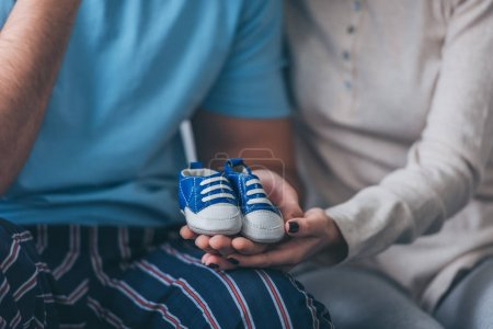 Photo for Cropped view of parents holding baby shoes at home - Royalty Free Image
