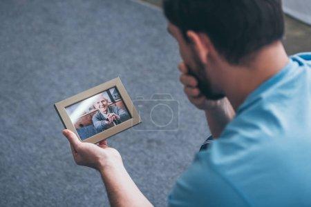 Foto de Vista posterior de adulto hombre afligido mientras mira en el marco de la foto con el anciano en casa - Imagen libre de derechos