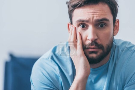 Photo for Handsome frightened man with hand on head looking at camera at home with copy space - Royalty Free Image