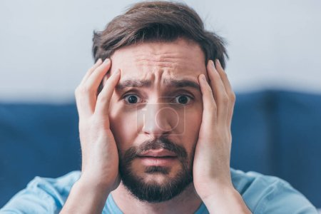 Photo for Selective focus of frightened man with hands on head looking at camera at home - Royalty Free Image