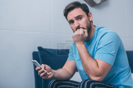 Photo for Upset man sitting on bed, covering mouth with hand and using smartphone at home - Royalty Free Image