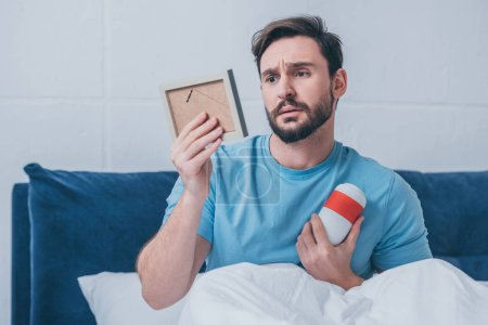 Photo for Sad man lying in bed and holding photo frame with funeral urn - Royalty Free Image