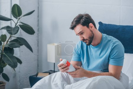 Photo for Depressed man looking at funeral urn in bed - Royalty Free Image