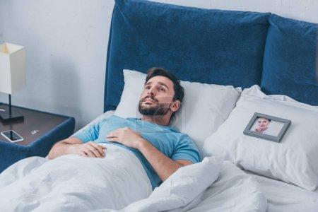 Foto de Hombre deprimido acostado en la cama cerca de marco de foto con foto de mujer en la almohada en casa - Imagen libre de derechos