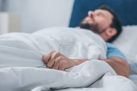 Photo for Man lying in bed and holding blanket - Royalty Free Image