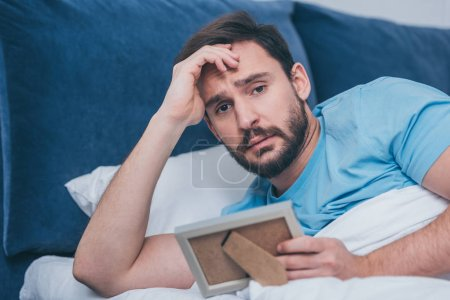 Photo for Upset man lying in bed, looking at camera and holding photo frame at home - Royalty Free Image