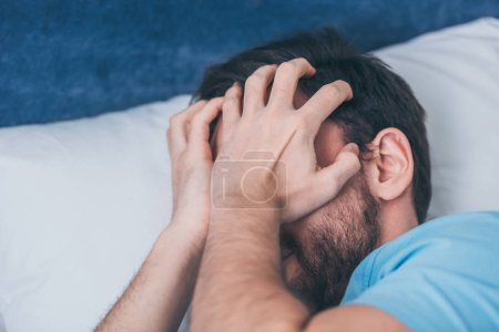 Photo for Grieving man lying in bed, covering face with hands and crying at home - Royalty Free Image