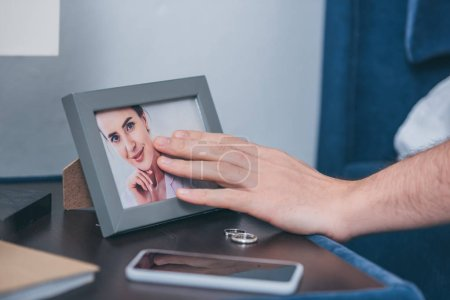 Photo for Cropped view of man touching photo frame with picture of woman near wedding rings and smartphone - Royalty Free Image