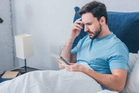 Photo for Upset man lying in bed and holding photo frame at home - Royalty Free Image