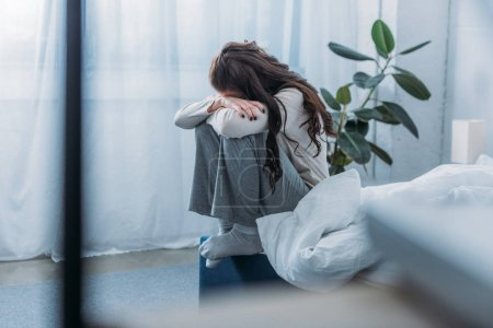 Photo for Grieving woman sitting, covering face with hands and crying in bedroom - Royalty Free Image