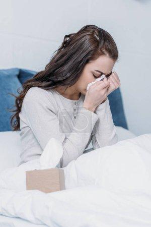 Photo pour Femme couchée au lit avec une boîte en tissu, pleurant et essuyant des larmes - image libre de droit