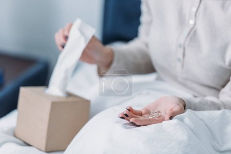 Photo for Partial view of woman lying in bed and holding wedding rings while reaching for tissue - Royalty Free Image