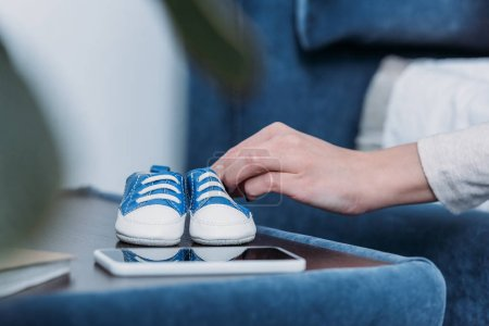 Photo for Cropped view of woman holding baby shoes at home - Royalty Free Image