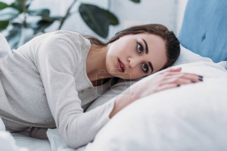 Photo for Selective focus of beautiful sad woman in pajamas lying in bed at home - Royalty Free Image