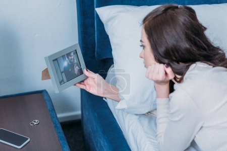 Foto de Upset woman lying in bed and looking at frame with picture of man at home - Imagen libre de derechos