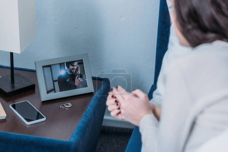 Photo for Cropped view of woman looking at frame with picture of man and wedding rings on nightstand - Royalty Free Image