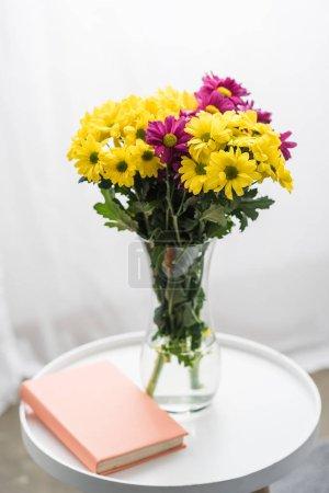 Photo pour Fleurs fraîches et livre sur tableau blanc - image libre de droit