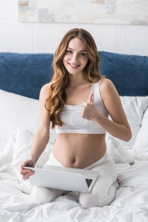 Curly pregnant woman using laptop in bed and showing thumb up