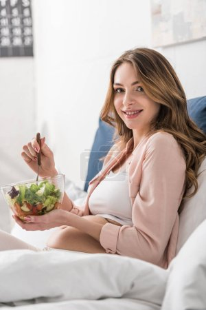 Photo for Laughing pregnant woman eating salad in bed - Royalty Free Image