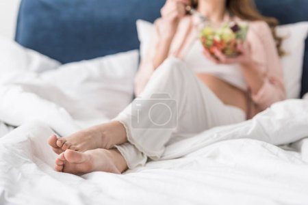 Photo for Partial view of barefooted pregnant woman eating salad in bed - Royalty Free Image