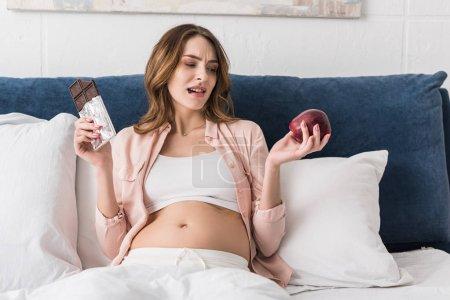 Femme enceinte hésitante tenant des barres chocolatées et des pommes