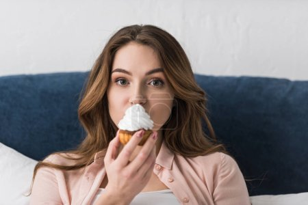 Photo for Brunette beautiful woman eating cupcake and looking at camera - Royalty Free Image
