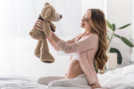 Photo pour Femme enceinte aux cheveux longs assise sur le lit et regardant un ours jouet - image libre de droit