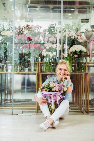 Photo for Beautiful smiling woman holding flower bouquet, looking at camera and sitting in front of flower shop - Royalty Free Image