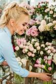 """Постер, картина, фотообои """"красивые улыбается женщина, выбирая цветы в цветочный магазин"""""""