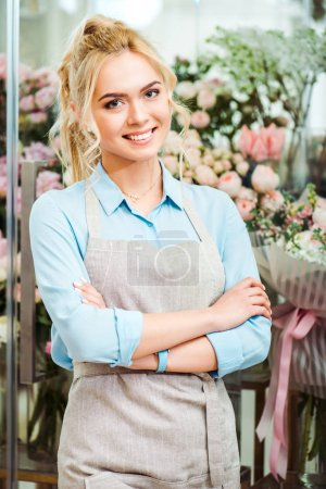 Photo for Beautiful smiling female florist in apron looking at camera with flower shop on background - Royalty Free Image