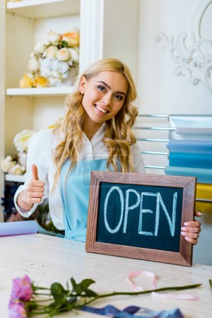 Photo for Beautiful female flower shop owner looking at camera, showing thumb up sign and holding chalkboard with 'open' lettering - Royalty Free Image