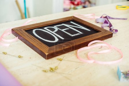 Photo for Selective focus of wooden chalk board with 'open' lettering on table with ribbons - Royalty Free Image