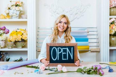 """Photo pour Belle femme souriante propriétaire de magasin de fleurs regardant caméra et tenant tableau avec lettrage """"ouvert"""" - image libre de droit"""