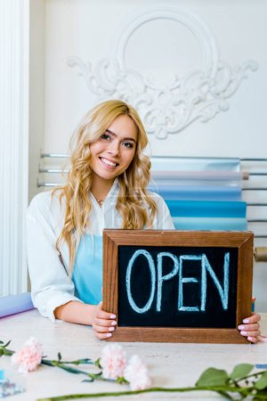 Photo for Beautiful smiling female flower shop owner looking at camera and holding chalkboard with 'open' lettering - Royalty Free Image