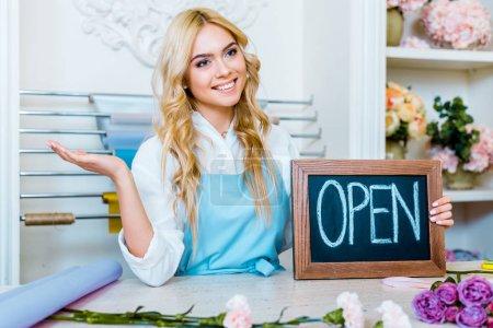 """Photo pour Belle femme souriante propriétaire de magasin de fleurs gestuelle avec la main et tenant tableau avec lettrage """"ouvert"""" - image libre de droit"""
