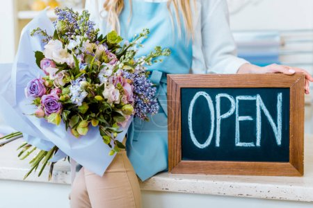 Photo for Cropped view of female flower shop owner holding chalkboard with 'open' lettering and colorful bouquet - Royalty Free Image