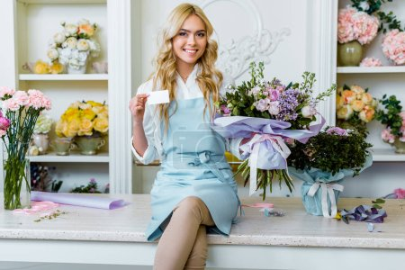 Foto de Beautiful smiling female flower shop owner sitting with bouquet, looking at camera and holding business card with copy space - Imagen libre de derechos