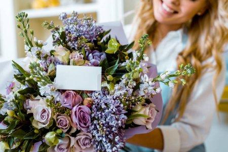 Photo pour Vue recadrée d'une femme et bouquet de fleurs avec roses, lilas et carte avec espace de copie - image libre de droit