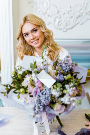 Photo for Selective focus of beautiful smiling woman with flower bouquet with roses, lilac and blank card on foreground - Royalty Free Image