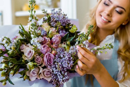 Photo for Smiling female florist arranging bouquet with lilac and roses in flower shop - Royalty Free Image