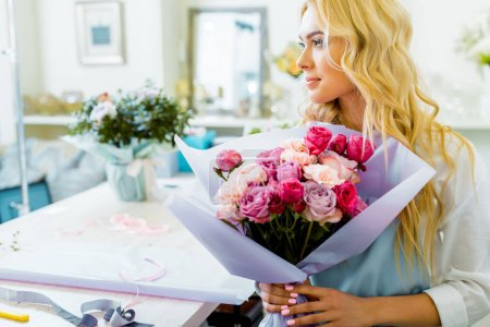 Photo for Beautiful female florist holding bouquet with roses and carnations in flower shop and looking away - Royalty Free Image