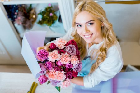 Foto de Beautiful female florist looking at camera while holding bouquet with roses and carnations in flower shop - Imagen libre de derechos