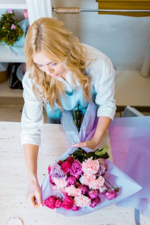 Photo for Beautiful female florist arranging bouquet with roses and carnations in flower shop - Royalty Free Image
