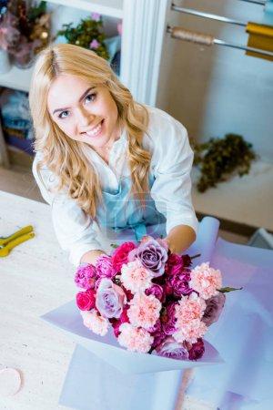 Foto de Bella sonriente a mujer Floreria arreglos bouquet con rosas y claveles en florería - Imagen libre de derechos