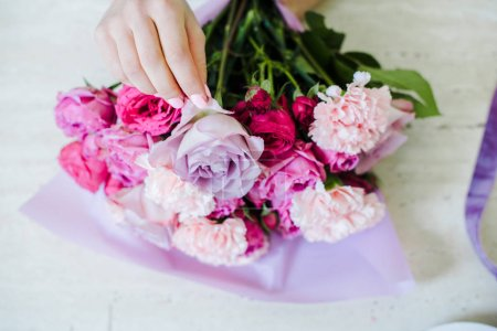 Photo for Cropped view of female florist arranging bouquet with pink roses and carnations - Royalty Free Image