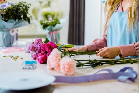 Photo for Cropped view of female florist sitting at table with pink roses and carnations while arranging bouquet - Royalty Free Image