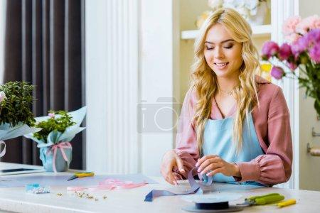 Foto de Hermosa Floreria mujer sonriente en el mostrador con fuentes decorativas y herramientas en la tienda de la flor - Imagen libre de derechos