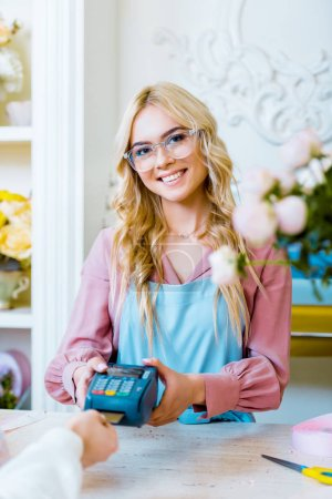 Photo for Customer paying with credit card in flower shop while beautiful female florist holding terminal - Royalty Free Image