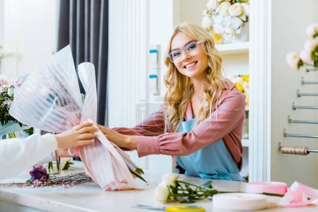 Photo for Beautiful smiling female florist giving bouquet to customer in flower shop - Royalty Free Image